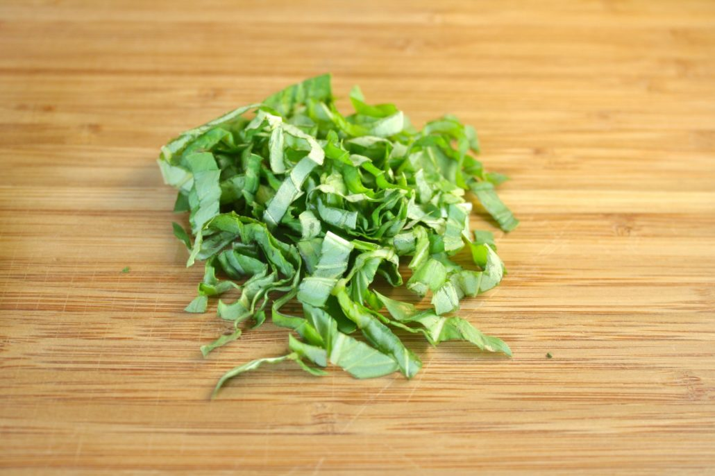 Learning how to chiffonade is our latest installment of fancy French cooking terms! Chiffonade is the term for cutting fresh herbs with large leaves into thin, ribbon-like strips. Basil is the perfect herb to for this, but you can also work with fresh mint or sage. Though it's most commonly used to refer to cut herbs, you can chiffonade any leafy food, like spinach, kale or lettuce. These thin strips are not only pretty on your plate, they make eating your leafy favorites easier, as well.